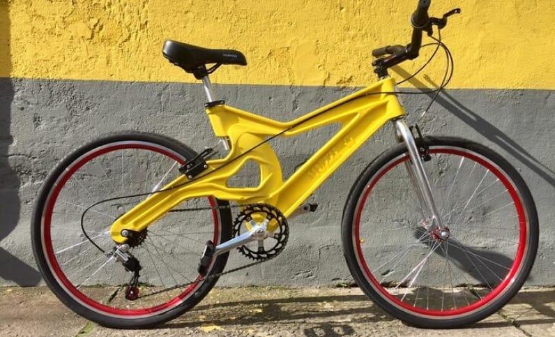 У стены стоит многоскоростной велосипед с желтой пластиковой рамой. Обода колес красного цвета.