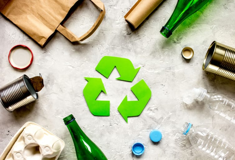 На бетонной поверхности кругом лежат различные материалы для вторичной переработки: консервные банки, стеклянные и пластиковые бутылки, бумажный пакет и картон. В центре круга - зеленый символ переработки отходов.